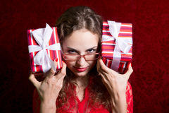 Young woman in glasses with two striped gift boxes stares into t Stock Photo