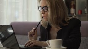 Young woman in glasses typing on keyboard notebook in cafe with coffee cup. Young woman in glasses typing on keyboard notebook sitting at couch in cafe with stock video