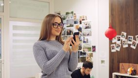 Young woman in glasses use smartphone in the office. Text message, online surfing, app, social network. Man on background stock video footage