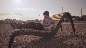 Freelancer with tablet sits on wooden deck chair on pebble beach in cool day. Young woman in glasses uses tablet while sitting on wooden deck chair on pebble stock footage