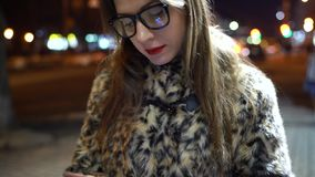 Young woman in glasses using smartphone on night city lights background stock footage