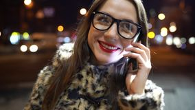 Young woman in glasses using smartphone on night city lights background stock video