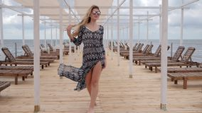 Young woman in glasses walks on wooden pier, expensive holidays of women on coast ocean, female in sunglasses stock footage
