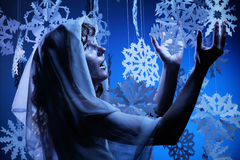 Young woman in glistering make up holding paper snowflake Royalty Free Stock Photo