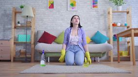 Young woman in gloves with discontent cleans the carpet with her hands