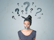 Young woman with glued mouth and question mark symbols Stock Photo