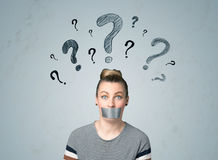 Young woman with glued mouth and question mark symbols Stock Photography