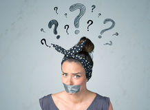 Young woman with glued mouth and question mark symbols Royalty Free Stock Photos