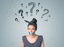 Young woman with glued mouth and question mark symbols Royalty Free Stock Image