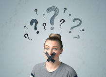Young woman with glued mouth and question mark symbols Stock Photos
