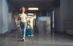 Young woman goes  at airport at window with suitcase waiting for Royalty Free Stock Photos