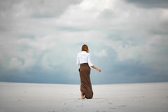 Young woman goes barefoot in desert. Back view. Royalty Free Stock Image