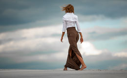 Young woman goes barefoot in desert on sky background. Back view Stock Photo