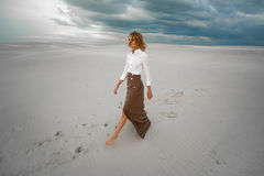 Young woman goes barefoot  in desert on sky background. Royalty Free Stock Photos
