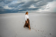 Young woman goes barefoot  in desert on sky background. Royalty Free Stock Image