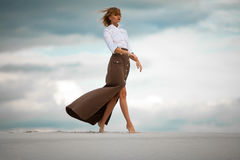 Young woman goes barefoot in desert on sky background. Side view Stock Photos
