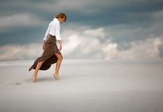 Young woman goes barefoot in desert on sky background. Side view Royalty Free Stock Photos