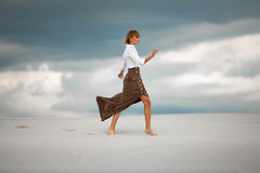 Young woman goes barefoot in desert on sky background. Side view Royalty Free Stock Photography