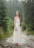 Young woman goes barefoot through the mountain river Royalty Free Stock Images