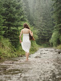 Young woman goes barefoot through the mountain river Stock Photos