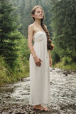 Young woman goes barefoot through the mountain river Stock Image