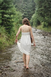 Young woman goes barefoot through the mountain river Royalty Free Stock Image