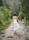 Young woman goes barefoot through the mountain river Royalty Free Stock Photo