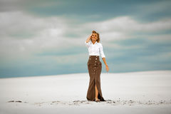 Young woman goes barefoot on sand in desert and smiles. Royalty Free Stock Photo