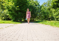 Young woman goes barefoot on the sidewalk Stock Photography