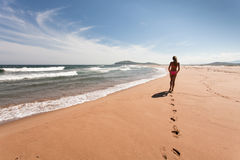 Young woman goes the distance through the empty, wild beach against a blue sky, yellow sand and sea. Wide angle. Stock Photo