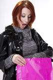 Young woman goes holiday shopping. A young redheaded woman looks into her holiday shopping bag stock image