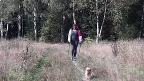 Young woman goes Nordic walking outdoors stock footage