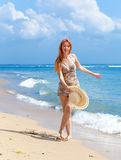 Young  woman goes on ocean coast  with hat Royalty Free Stock Photo