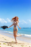Young  woman goes on ocean coast  with hat.Portrait Royalty Free Stock Images