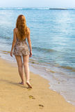 Young woman goes on Oceanside Royalty Free Stock Photography
