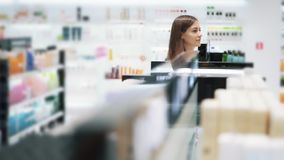 Young woman goes among shelves in cosmetics shop, slow motion, steadicam shot. Beautiful young woman with basket goes among shelves in cosmetics shop, slow stock video footage