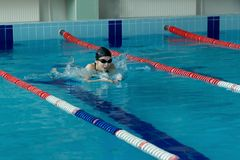 Young woman in goggles and cap swimming breaststroke stroke style in the blue water indoor race pool Stock Photos
