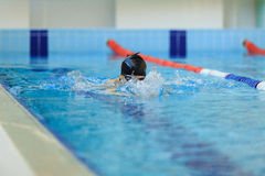 Young woman in goggles and cap swimming breaststroke stroke style in the blue water indoor race pool. Royalty Free Stock Photography