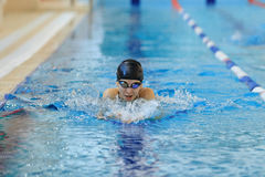 Young woman in goggles and cap swimming breaststroke stroke style in the blue water indoor race pool. Stock Photo