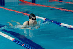 Young woman in goggles and cap swimming breaststroke stroke style in the blue water indoor race pool Royalty Free Stock Image