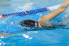 Young woman in goggles and cap swimming front crawl stroke style in the blue water indoor race pool. Stock Photography