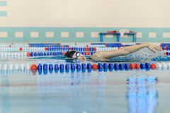 Young woman in goggles and cap swimming front crawl stroke style in the blue water indoor race pool. Royalty Free Stock Image