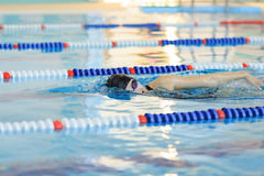 Young woman in goggles and cap swimming front crawl stroke style in the blue water indoor race pool. Royalty Free Stock Photography
