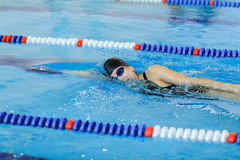 Young woman in goggles and cap swimming front crawl stroke style in the blue water indoor race pool Stock Photo