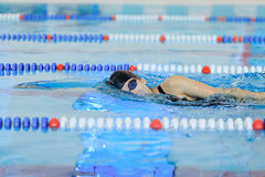 Young woman in goggles and cap swimming front crawl stroke style in the blue water indoor race pool. Stock Photo