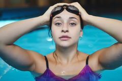 Young woman with goggles in a swimming pool. Royalty Free Stock Photos