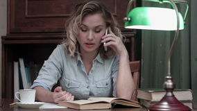 Young woman going through a book and having an angry phone conversation sitting at her desk stock video footage