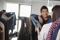 Young woman going through scarfs at fashion store Stock Photo