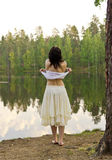 Young woman going to swim in forest lake Stock Photo