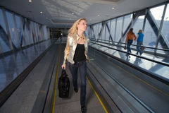 Young woman going on the travelator in a hurry Stock Photography